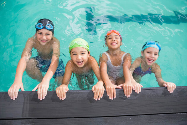 Four kids hanging off the side of the pool