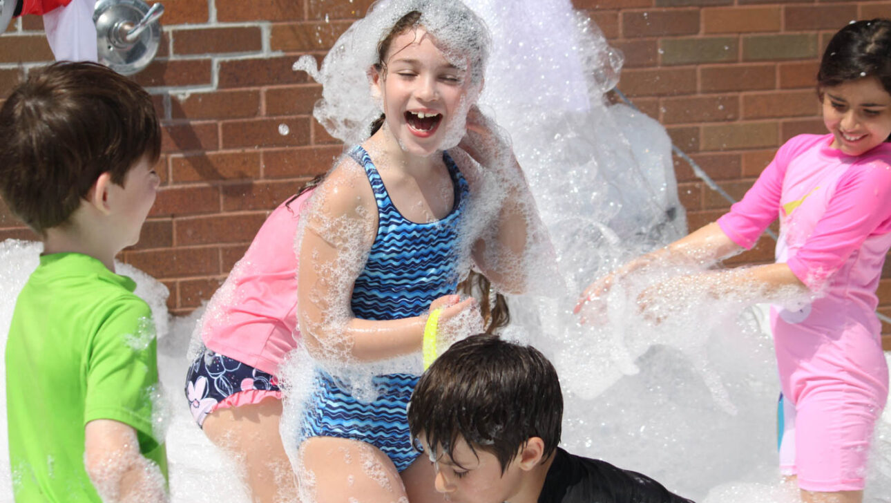 Girl covered in bubbles.
