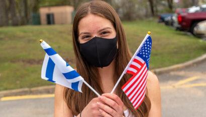 Teen girl holding and American flag and an Israeli flag.