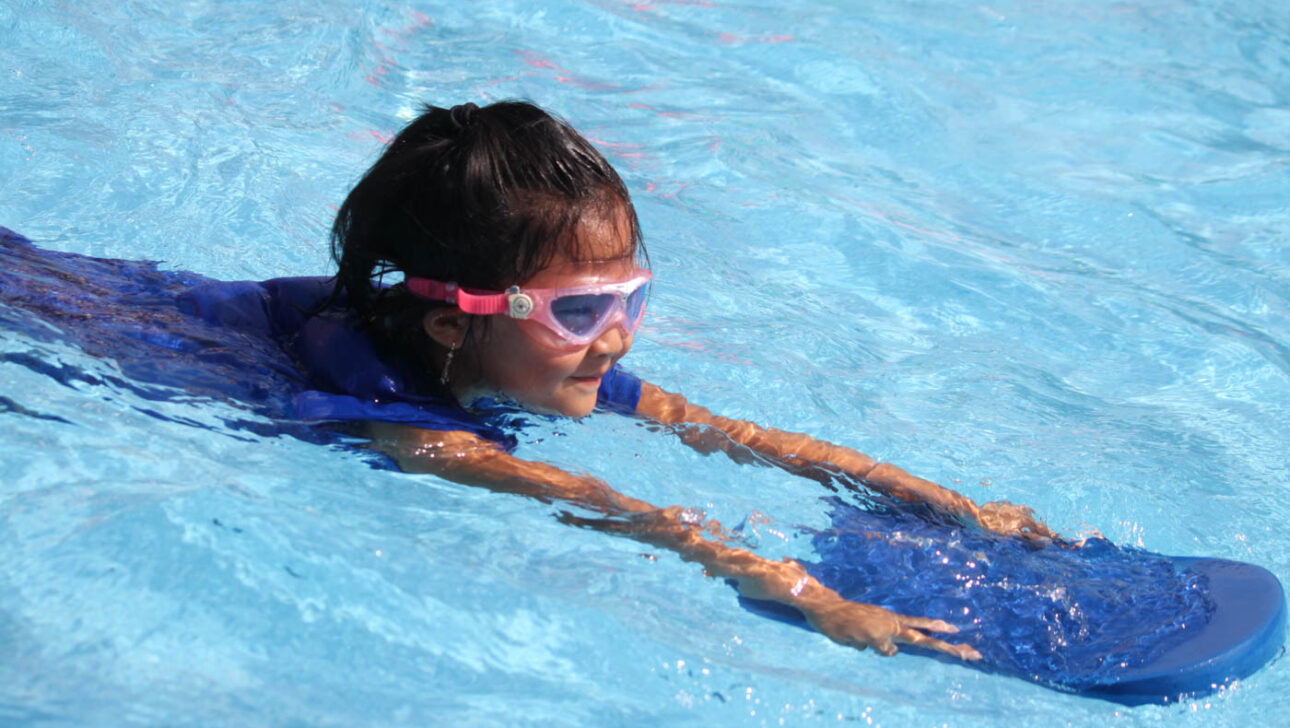 Girl swimming in the pool with a kick board.