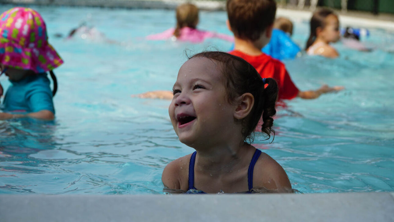 Young girl smiling in the pool.