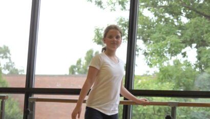 Girl using the barre to practice dance.