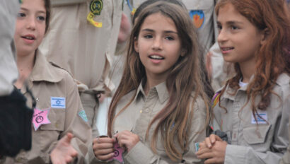 Girls in scout uniforms hanging out together.