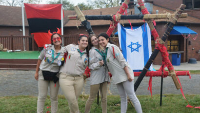 Girls standing next to an Israeli flag.