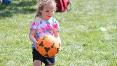 Girl holding a soccer ball.