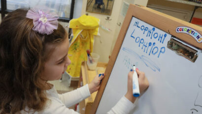 Child writing on a white board.