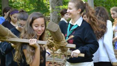 Girls carrying a wooden frame.