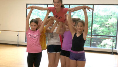 Group of girls holding up another girl in the air.