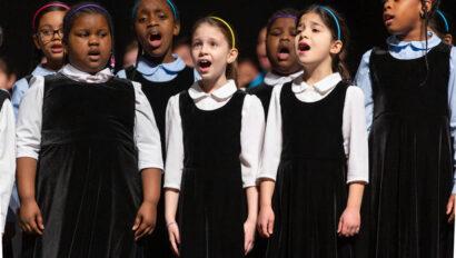 Children singing on stage.