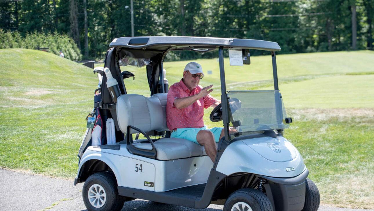 Man driving a golf cart.