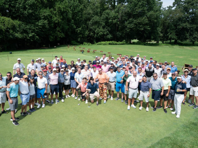 Large group photo on a golf course green.