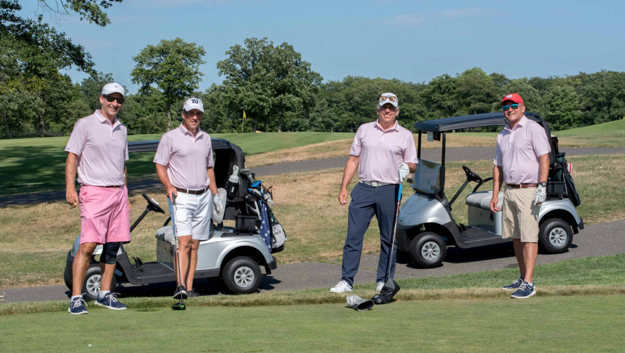 Four men standing next to golf carts.