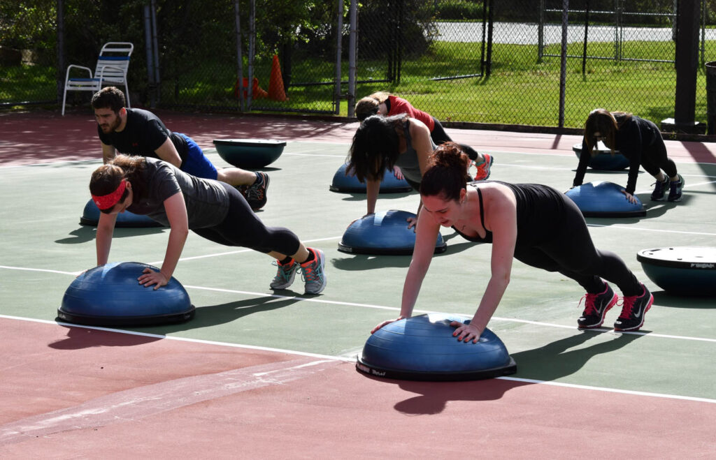 Group outside class doing planks on stability balls.