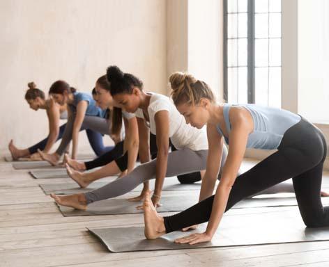 Group of women practicing yoga lesson, doing Ardha Hanumanasana exercise.