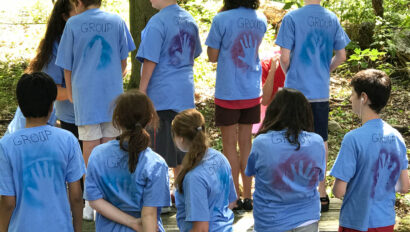 Campers with shirts with handprints on them.