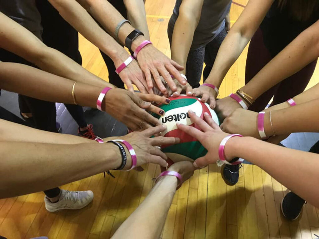 Team huddle with hands all touching a volleyball in the middle.