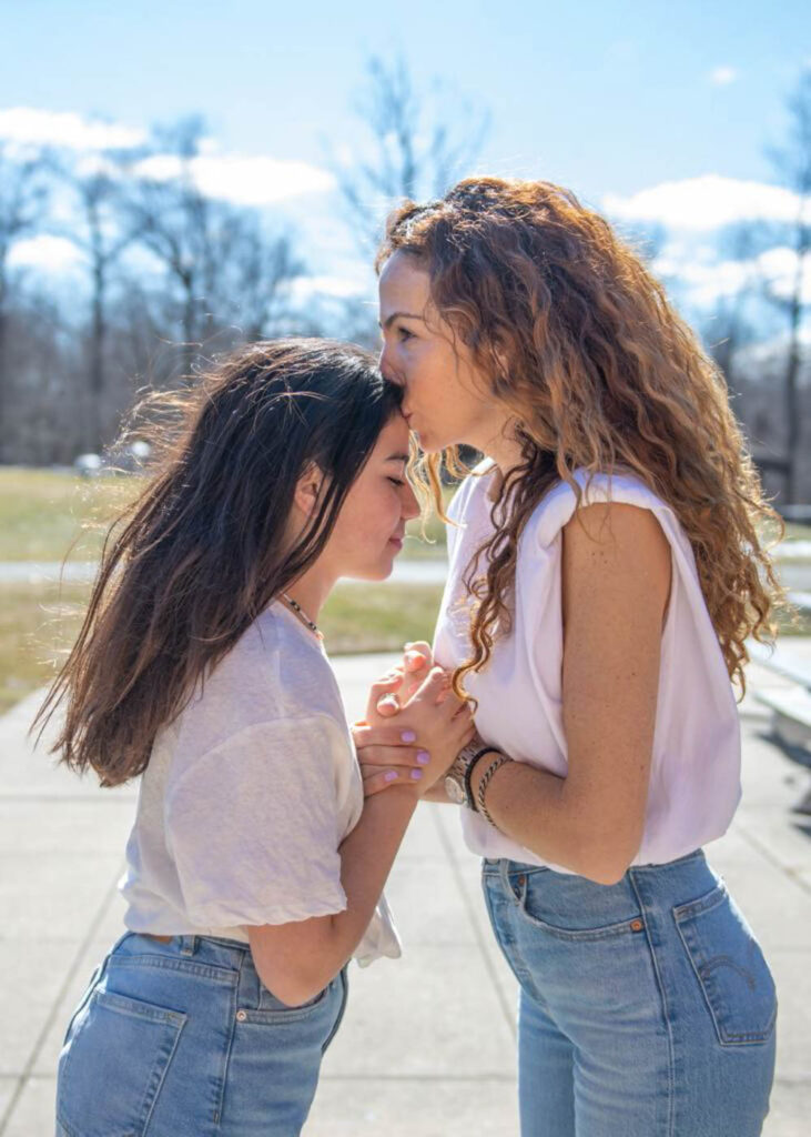 Older girl kissing a younger girl on the forehead.