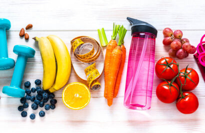 Colorful assortment of health food and water bottles and workout gear.