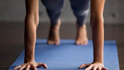 Woman doing a high plank on a yoga mat.