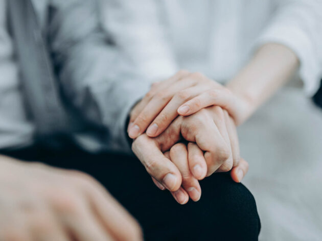 One person putting their hand on another persons hand in support group.