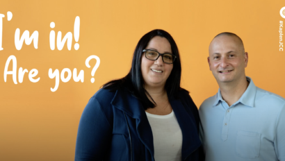 """couple standing in front of an orange background with the words """"I'm in! Are you?""""."""