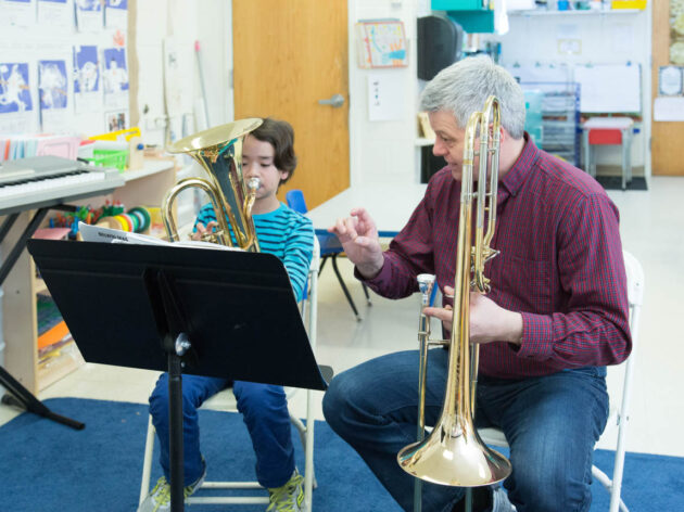 Teacher giving a horn lesson to a young boy.