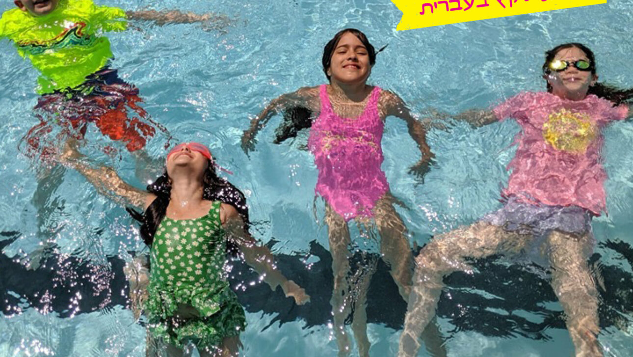 Group shot of children smiling and swimming in a pool.