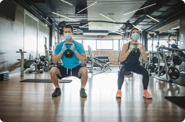 Man and woman doing squats with kettle bells.