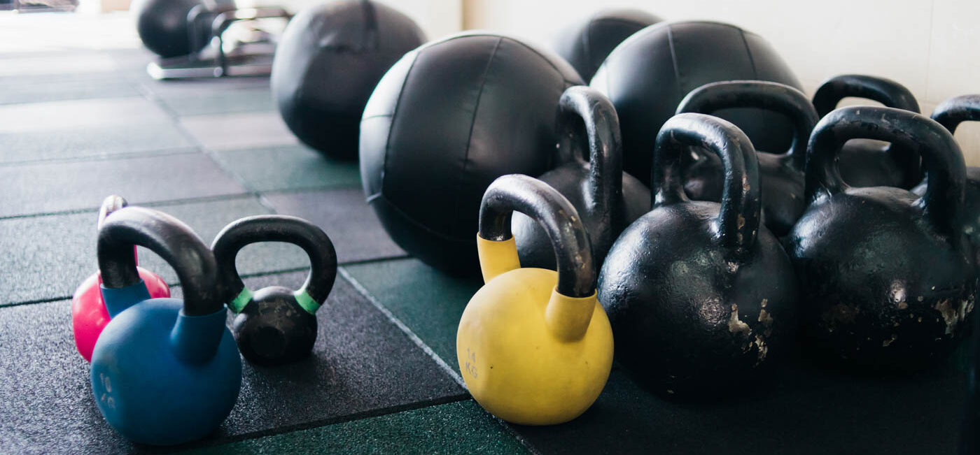 Kettlebells and medicine balls lined up on the floor.
