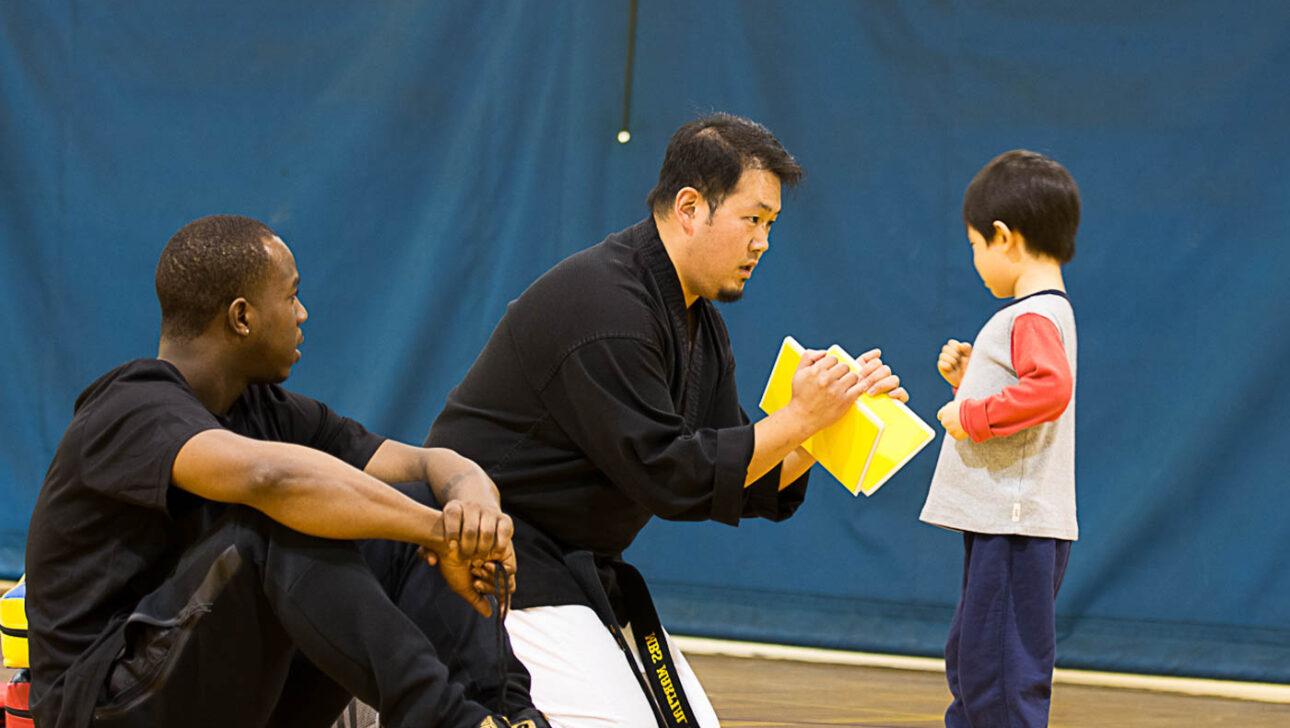 Young boy karate chopping a board.