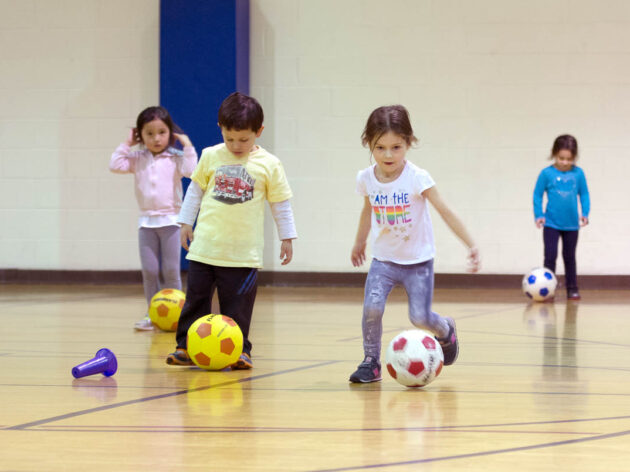 Kids playing soccer in a gym.