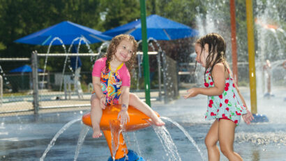 Two kids playing on a water playground.