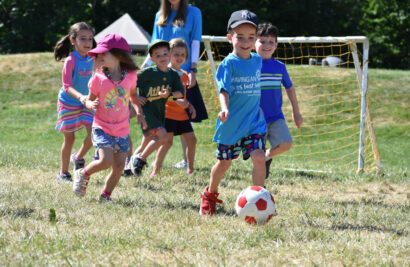 Young kids running and playing soccer.