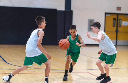 three boys playing basketball on a court.