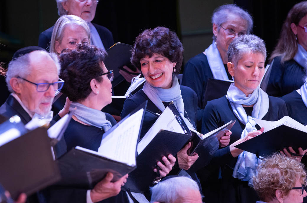 Women in choir smiling at each other.