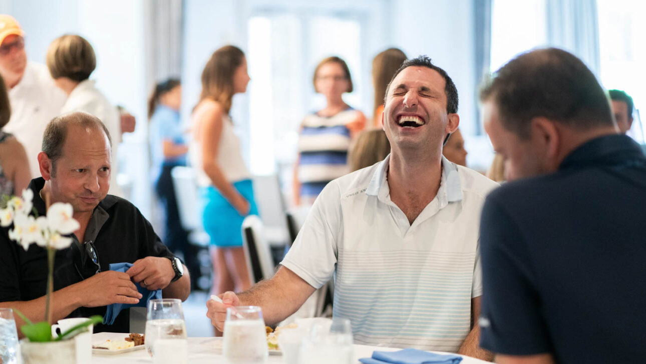 Man laughing at lunch table.
