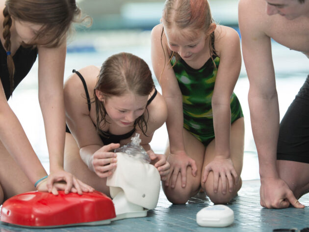 Girls learning how to do CPR on a dummy.