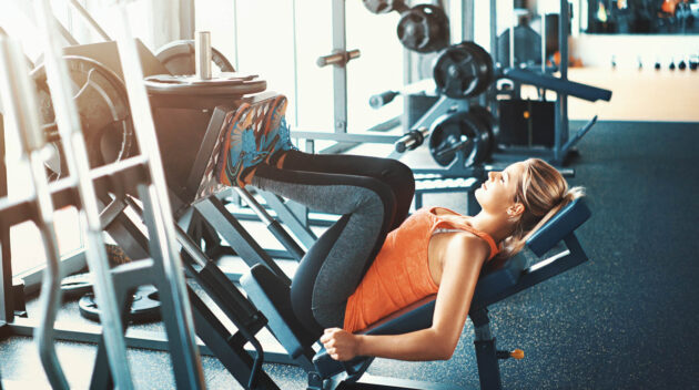 Woman using the leg press machine in the gym.
