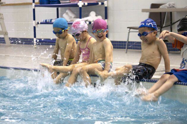 Children practicing kicking in a pool