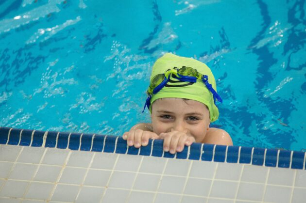 Child peaking over the edge of a pool