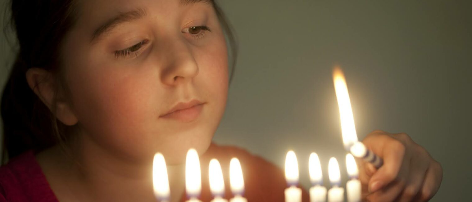 Girl, age 11, lights a menorah.