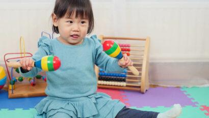 Baby girl playing with maracas.