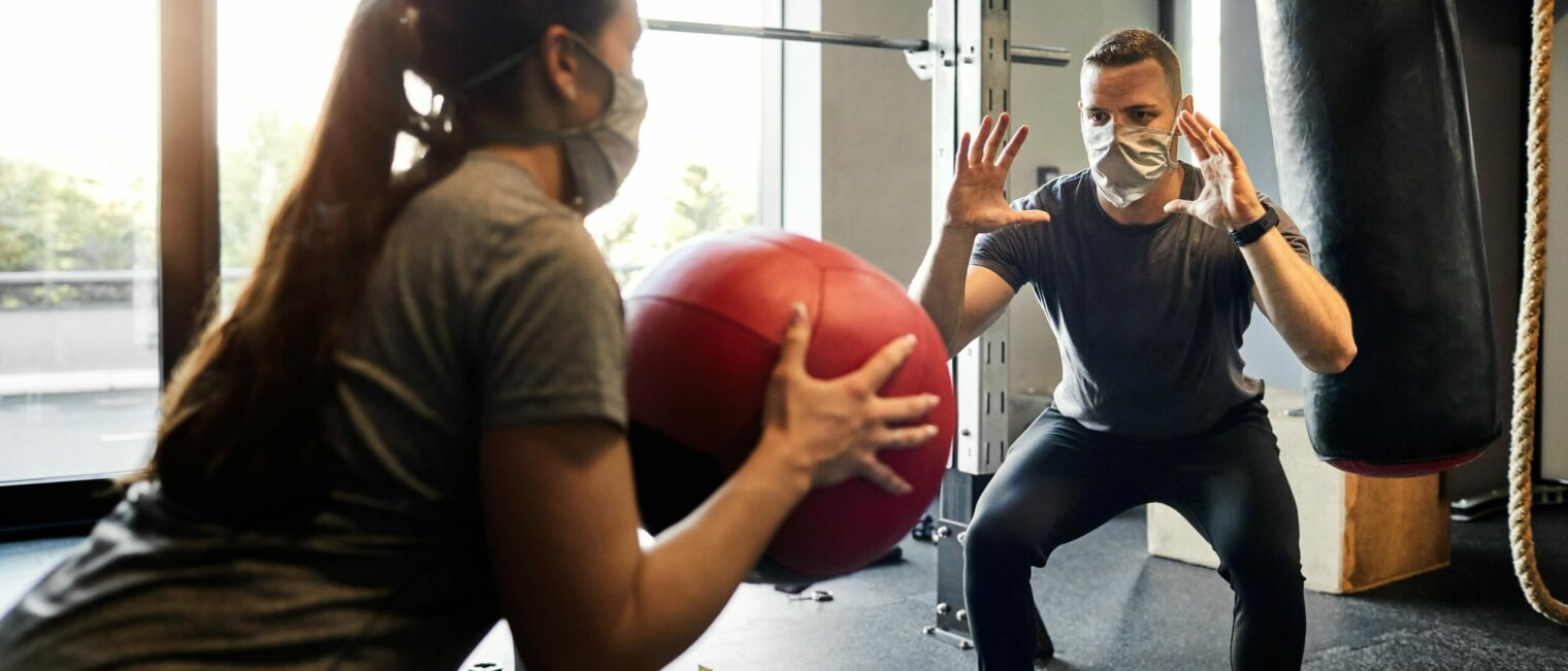 Young Woman Exercising In The gym With Assistance From Her Personal Trainer During Coronavirus Pandemic.