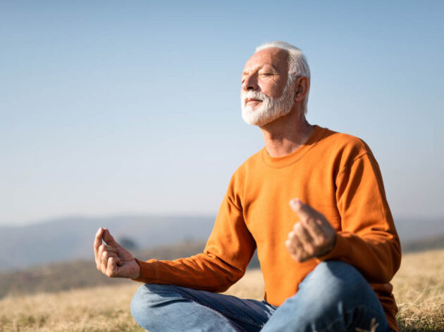 Senior man meditating outside.