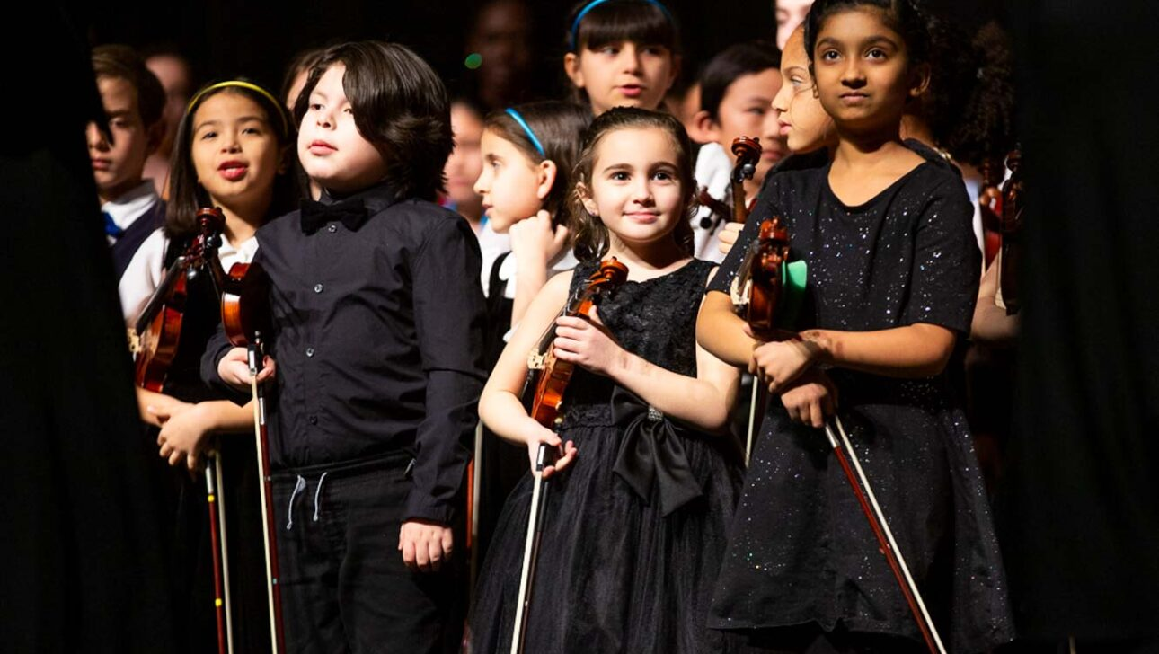 Performers ready to play their instruments onstage.