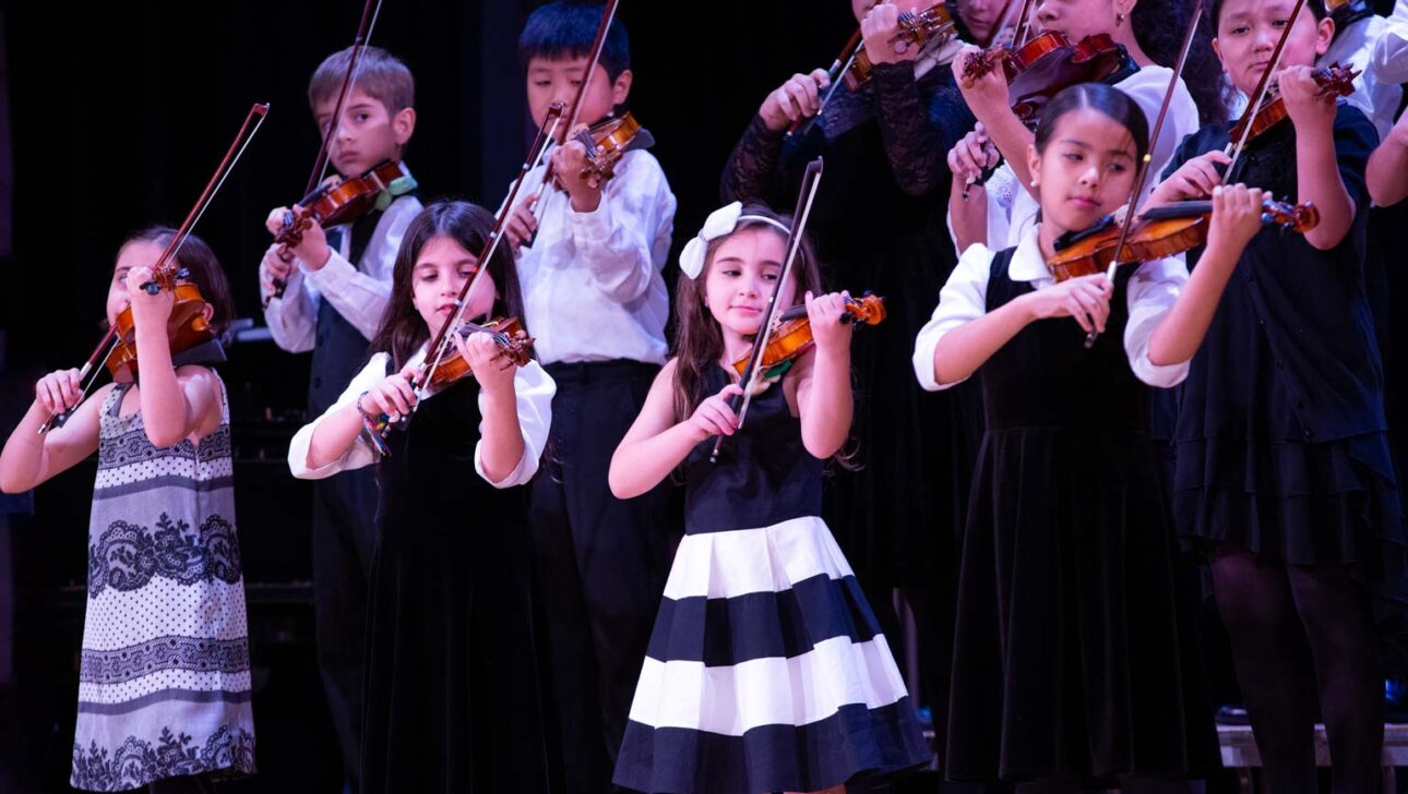 Children performing violins onstage.