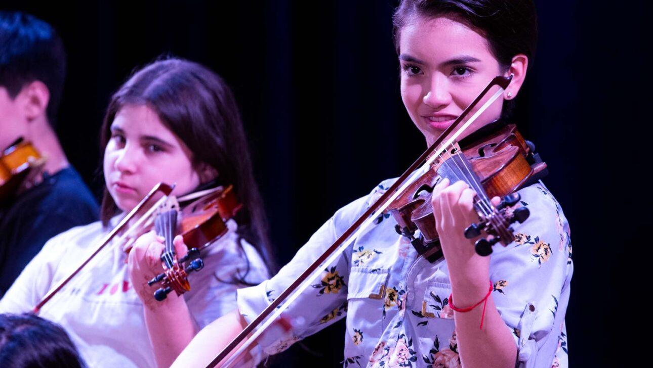 Girls playing violins onstage.