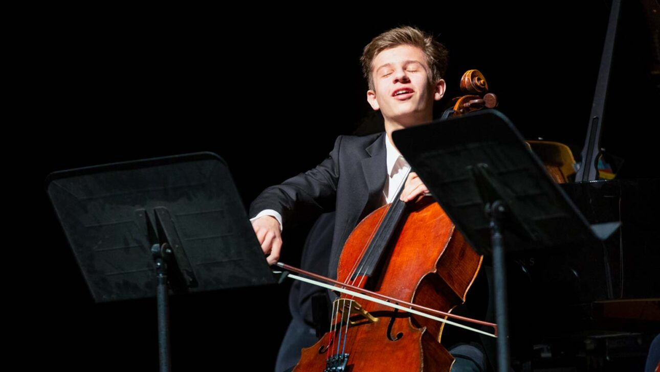 Boy playing a cello onstage.