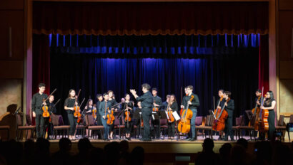 Orchestra bowing on stage.