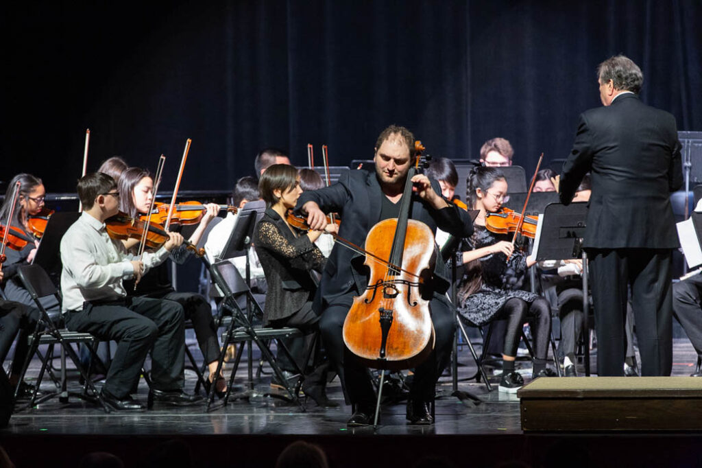 Cellist playing with an orchestra on stage.